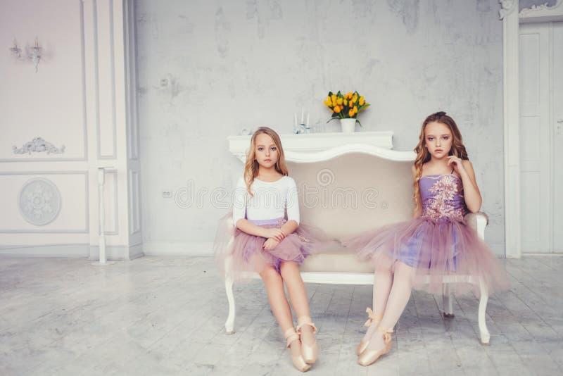 Wenig Mädchen, das im Ballettstudio mit Kopienraum sitzt stockfotografie