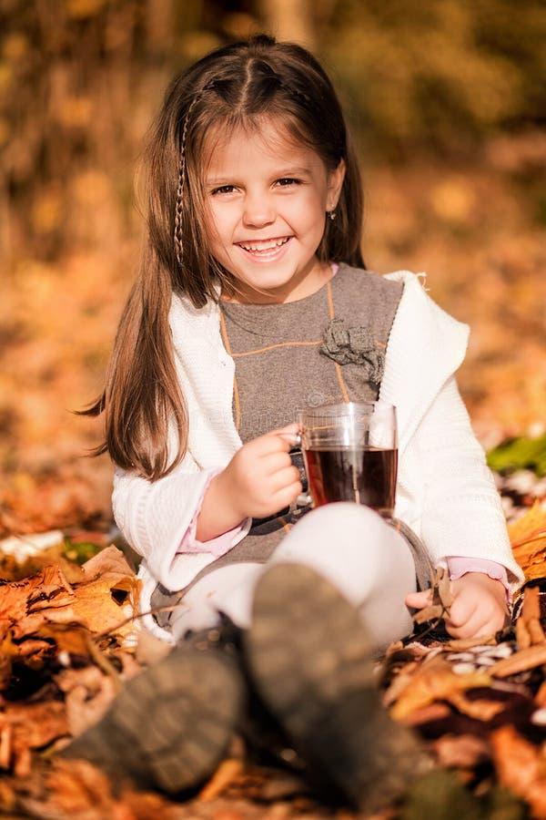 Wenig Mädchen, das im Wald mit einem Becher heißem Tee unter den gelben Blättern sitzt lizenzfreie stockfotos