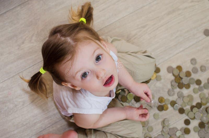Wenig Mädchen, das mit Münzen zählt lizenzfreie stockbilder