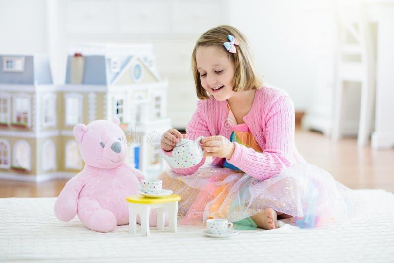 Wenig Mädchen, das mit Puppenhaus spielt Kind mit Spielwaren stockbild