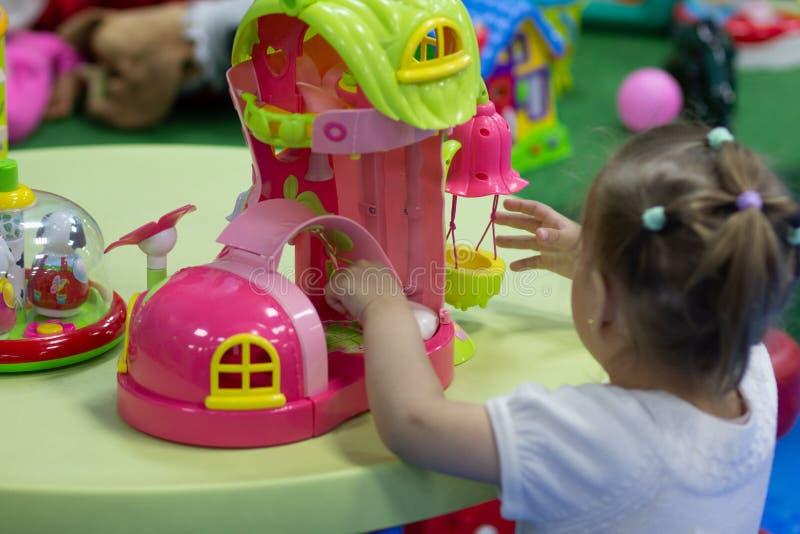 Wenig Mädchen, das mit Spielzeugschuh im Spielraum spielt stockfoto