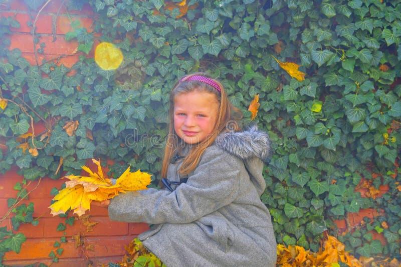 Wenig Mädchen, das Retro- Mantel trägt und vor Backsteinmauer im Herbst sich duckt Efeuwand im Herbst Getrennt auf Weiß Abstrakte stockbild