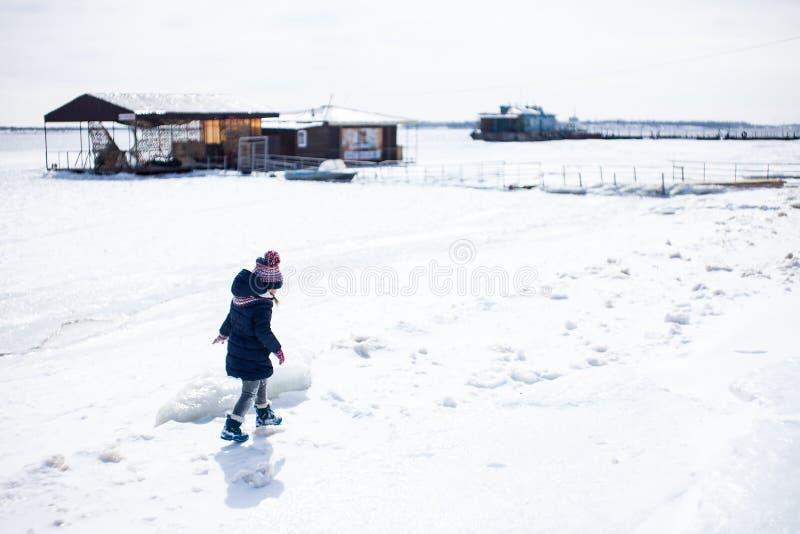Wenig Mädchen, das in Schnee in den warmen Stoffen geht stockbilder