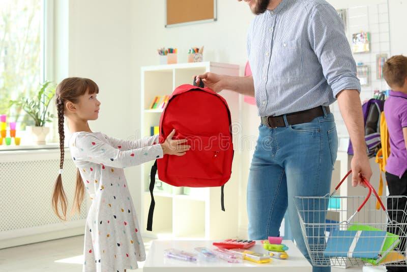 Wenig Mädchen, das Schulbedarf mit Vater im Geschäft wählt stockfoto