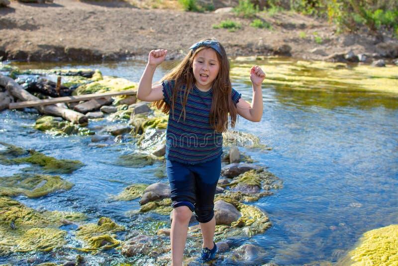 Wenig Mädchen, das sorgfältig einen Strom an einem Park kreuzt lizenzfreies stockfoto