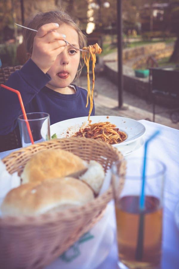 Wenig Mädchen, das Teigwarenspaghettis isst stockfotos