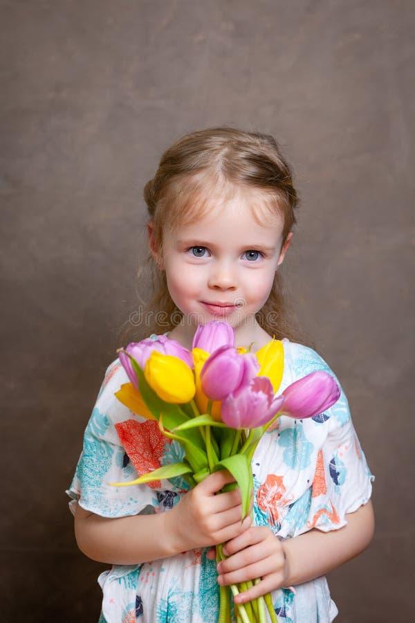 Wenig Mädchen, das Tulpen hält lizenzfreies stockfoto
