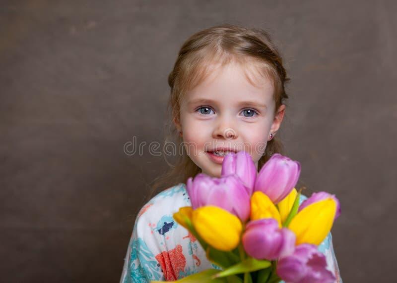 Wenig Mädchen, das Tulpen hält stockbild