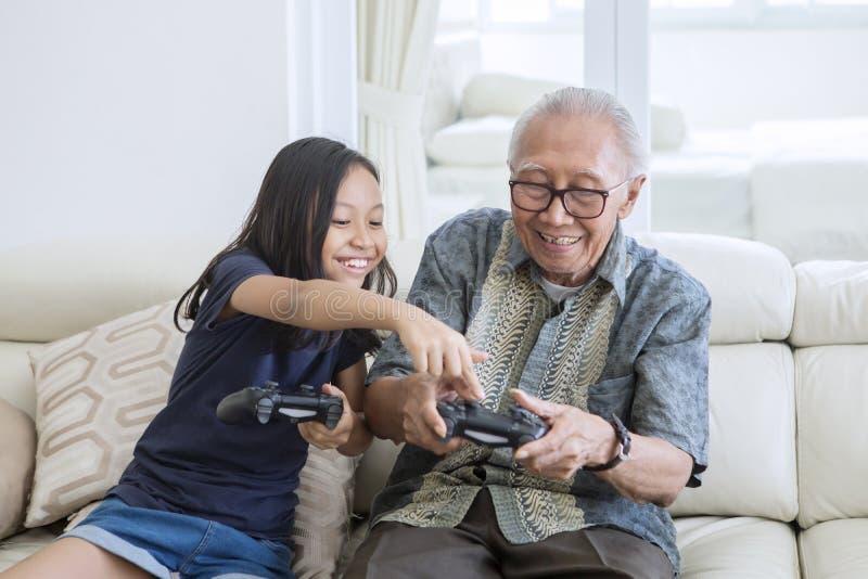 Wenig Mädchen, das Videospiele mit ihrem Großvater spielt stockbilder