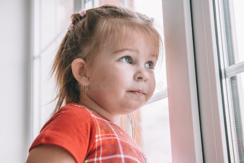 Wenig Mädchen in den Pyjamas, die heraus das Fenster dem ersten Schnee betrachten lizenzfreie stockbilder
