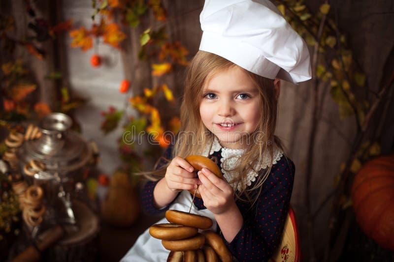 Wenig Mädchen in der Kochkleidung mit Bageln in ihren Händen und in Lächeln stockbild
