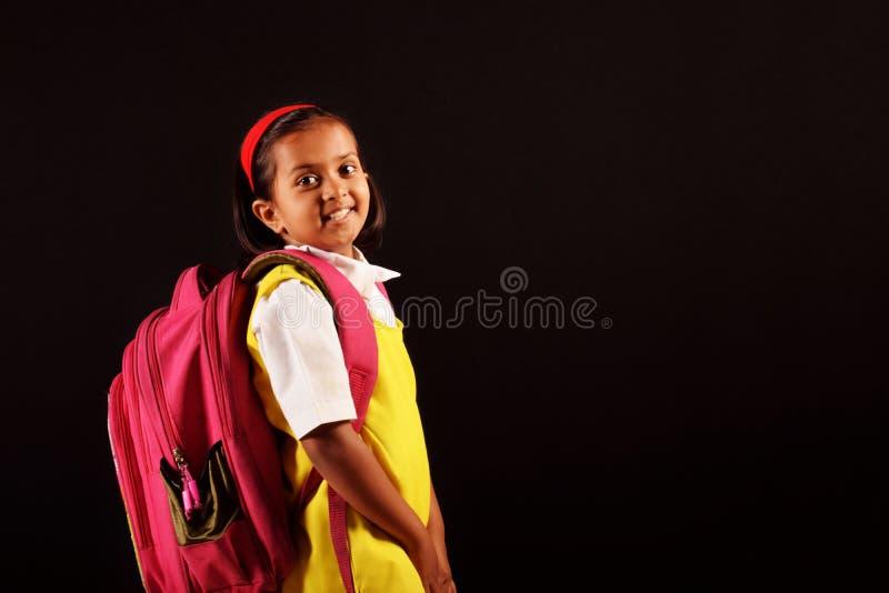 Wenig Mädchen in der Schuluniform und in der Tasche und tiffin, das vor Kamera aufwirft Pune, Maharashtra stockbild