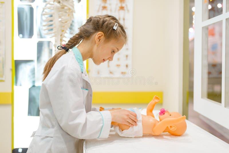 Wenig Mädchen in der Uniform, die Doktor mit Puppe spielt lizenzfreie stockfotos