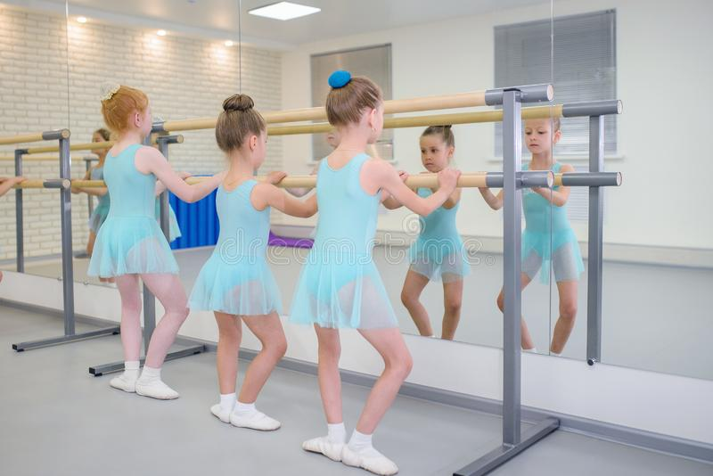 Wenig Mädchen, die Ballett im Studio nahe Barre üben Konzentration auf Übung, Ansicht von der Rückseite lizenzfreies stockbild