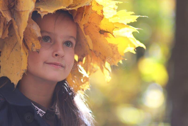 Wenig Mädchen in einem Kranz des gelben Herbstlaubs lizenzfreies stockbild