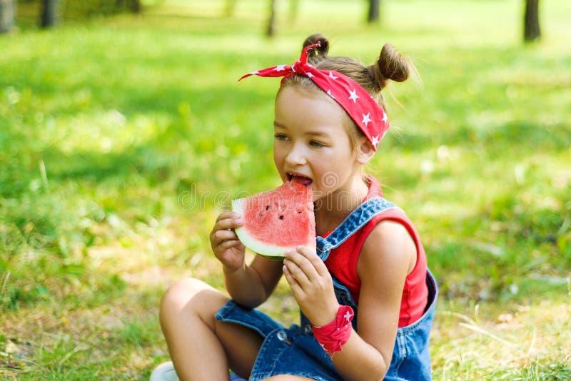Wenig Mädchen in einem roten T-Shirt und ein Kopftuch in einem Denimoverall, der eine reife Wassermelone hält stockbild