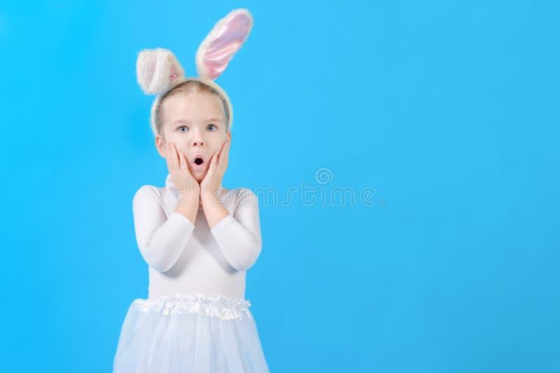 Wenig Mädchen in einem weißen Kaninchenkostüm Überraschtes Schätzchen Nettes Häschen, Feiertagssymbol Helles Foto auf einem blaue stockbild