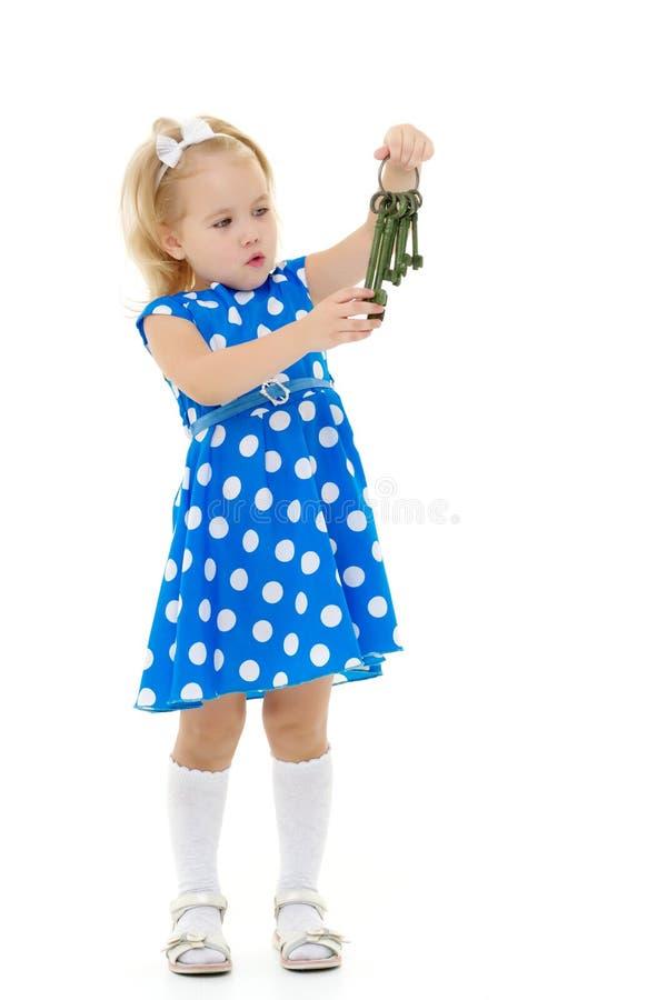 Wenig Mädchen hält Schlüssel zur Tür lizenzfreie stockbilder