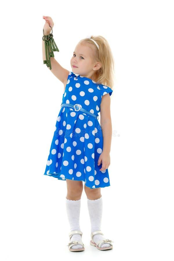 Wenig Mädchen hält Schlüssel zur Tür stockbild