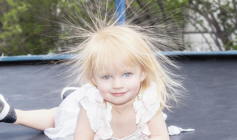 Wenig Mädchen-Kleinkind spielt auf einer Trampoline und hat statisch Elektrizität in ihrem Haar stockfotos