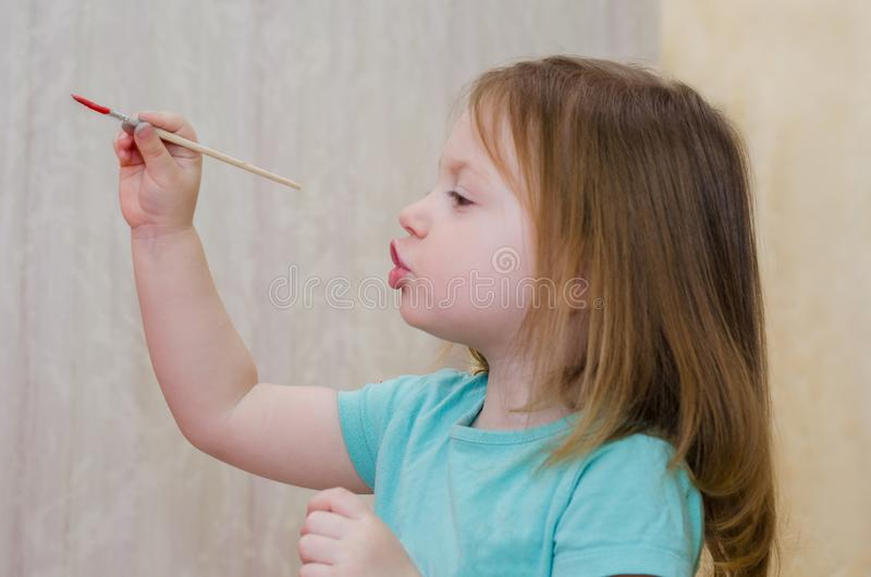 Wenig Mädchen malt durch Bürste stockfotografie