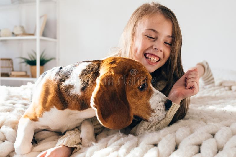 Wenig Mädchen mit dem Hund, der auf Bett und dem Lachen liegt lizenzfreie stockbilder