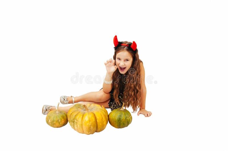 Wenig Mädchen mit dem langen Haar in einem Teufelkleid in einem Kleid mit Hörnern auf Halloween mit Kürbisen stockfotografie