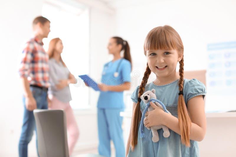 Wenig Mädchen mit den Eltern, die den Doktor der Kinder besuchen stockfoto
