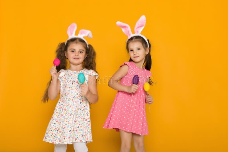 Wenig Mädchen mit den Osterhasenohren, die bunte Eier halten stockfotografie