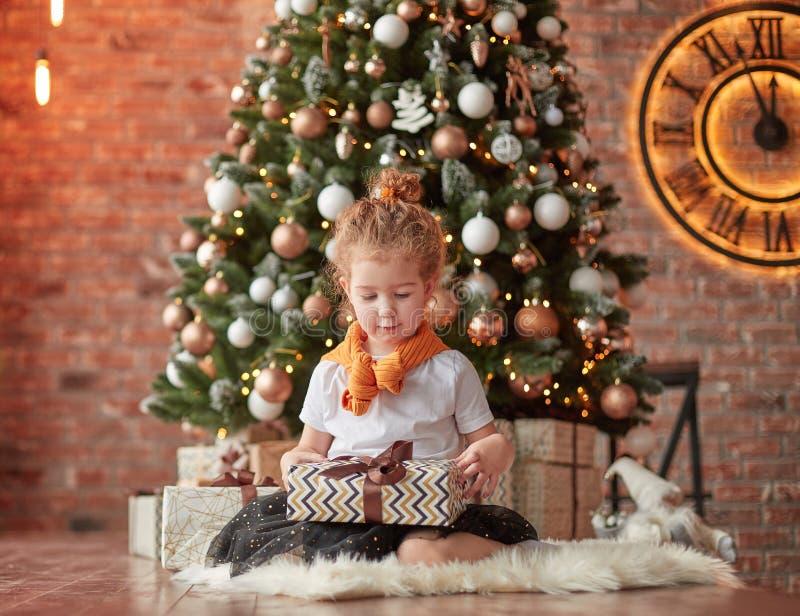 Wenig Mädchen mit den Weihnachtsgeschenken, die nahe dem Weihnachtsbaum sitzen lizenzfreie stockbilder