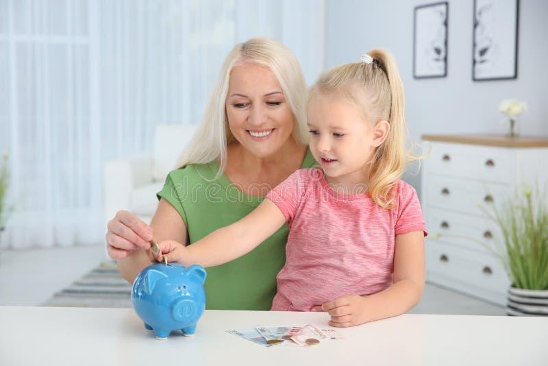 Wenig Mädchen mit der Großmutter, die Geld in Sparschwein steckt lizenzfreies stockbild