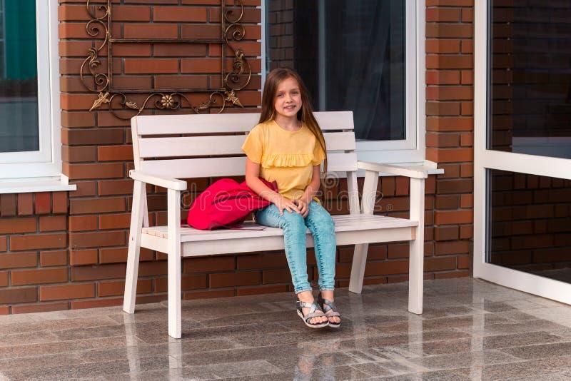 wenig Mädchen mit einem Rucksack, der auf einer Bank vor einer Backsteinmauer sitzt lizenzfreie stockfotografie