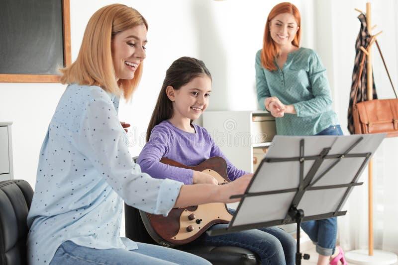 Wenig Mädchen mit ihrem Lehrer und Mutter am Musikunterricht lizenzfreies stockfoto
