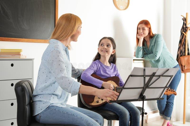Wenig Mädchen mit ihrem Lehrer und Mutter am Musikunterricht lizenzfreie stockbilder