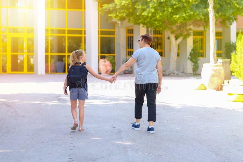 Wenig Mädchen mit Schultasche oder Schultasche, die zur Schule mit Großmutter gehen R?ckseitige Ansicht lizenzfreies stockbild