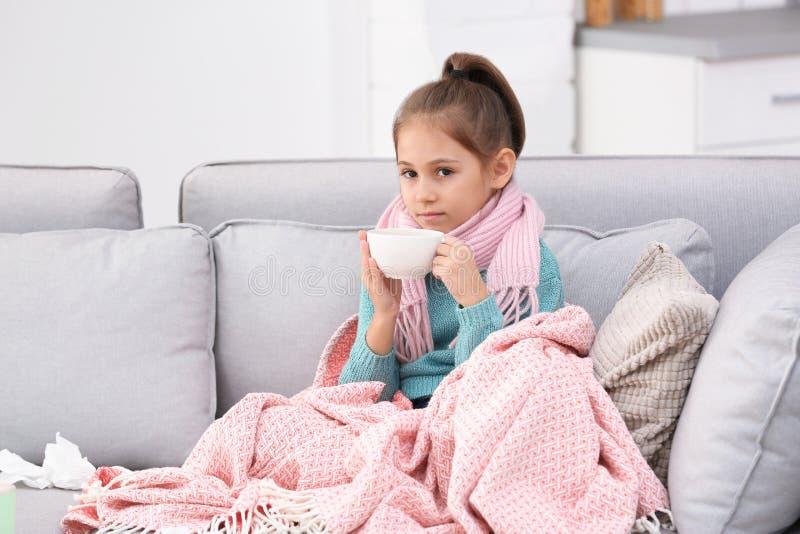 Wenig Mädchen mit Tasse Tee für Husten auf Sofa stockbilder