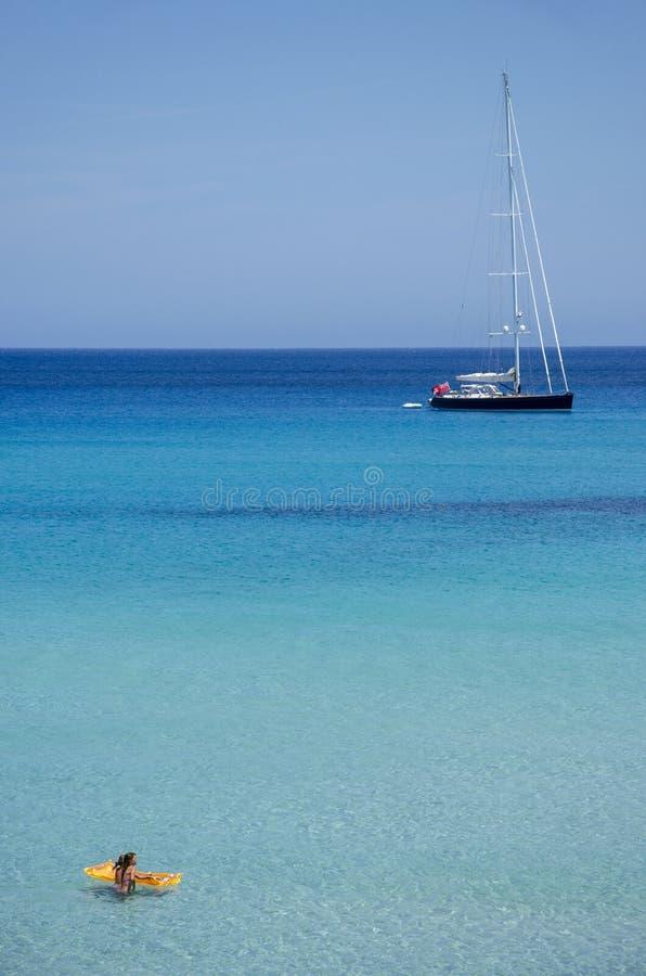 Wenig Mädchen mit waterbeds und Segelboot Majorca, die Balearischen Inseln, Spanien lizenzfreie stockfotografie