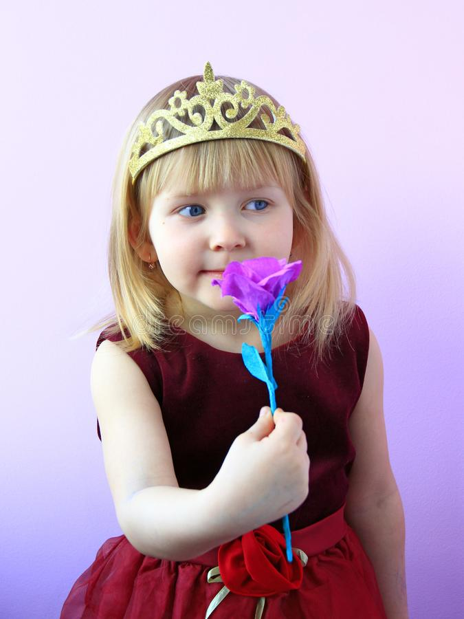Wenig M?dchen in riechender Blume der Krone r lizenzfreie stockfotos
