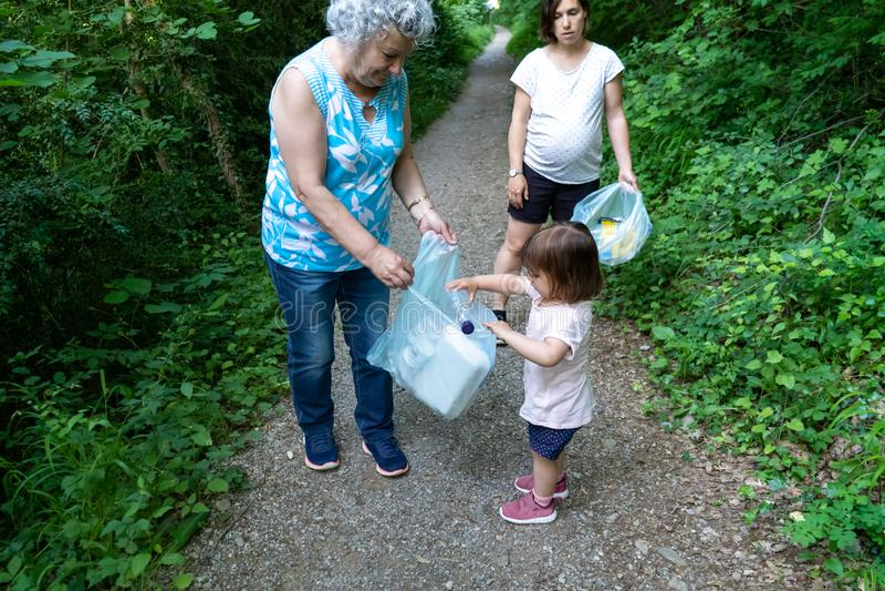Wenig Mädchen, schwangere Mutter und Großmutter, die den Wald des Plastiks säubert stockfotos