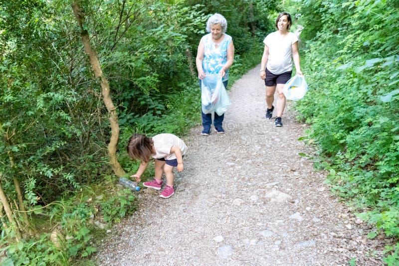 Wenig Mädchen, schwangere Mutter und Großmutter, die den Wald des Plastiks säubert stockbild