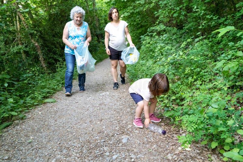 Wenig Mädchen, schwangere Mutter und Großmutter, die den Wald des Plastiks säubert lizenzfreies stockbild