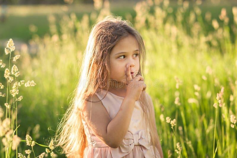 Wenig Mädchen setzte einen Finger zu ihren Lippen stockfotografie