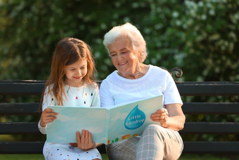 Wenig Mädchen und ihr Großmutterlesebuch auf Bank stockfotos