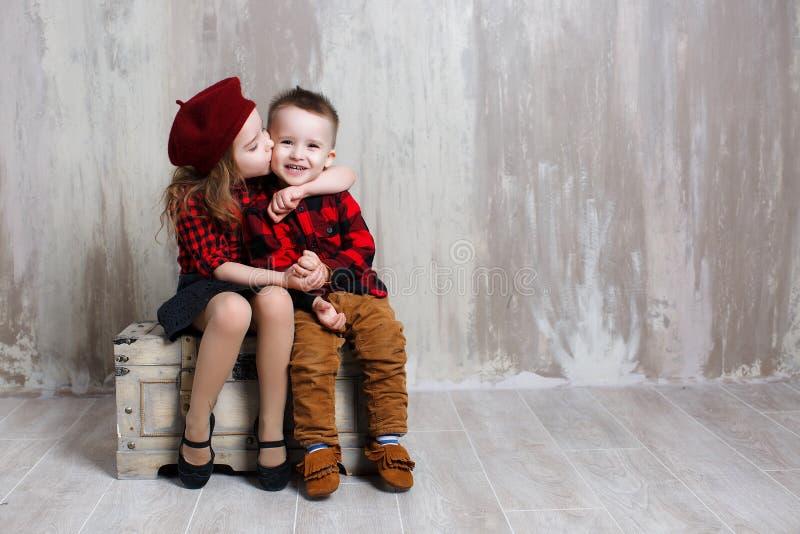 Wenig Mädchen und Junge, die auf einem alten Kasten im Studio auf einem grauen Hintergrund sitzen lizenzfreies stockfoto