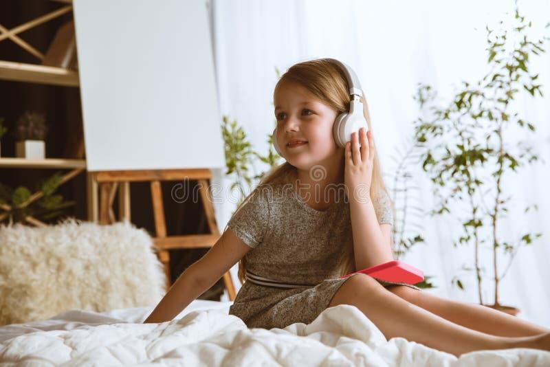 Wenig Mädchen unter Verwendung der verschiedenen Geräte zu Hause lizenzfreie stockfotografie