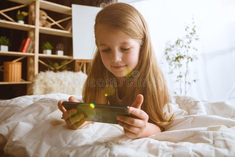 Wenig Mädchen unter Verwendung der verschiedenen Geräte zu Hause stockbilder