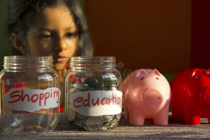Wenig Mädchen, welches die Geldgläser beschriftet als Einkaufen und Ausbildung mit Sparschweinen, Pune, Indien betrachtet stockbilder