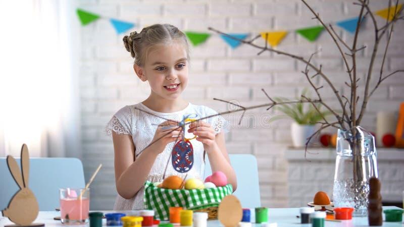 Wenig Mädchen, welches die handgemachten Spielzeugeier, Baumast verzierend, Ostern-Feiertag hält stockbild