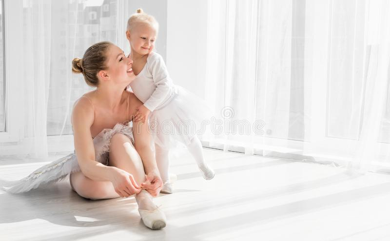 Wenig Mädchen wird unterrichtet, wie man Ballett pointe Schuhe bindet lizenzfreie stockfotos