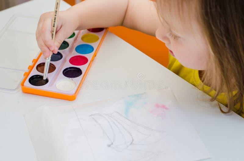 Wenig Mädchen zeichnet mit Aquarellen stockfotografie